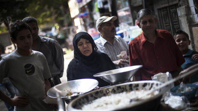 An Egyptian woman waits for her breakfast on a street fast food restaurant in Suleiman Gohar market in Dokki district in Cairo, Egypt, Monday, Aug. 26, 2013. Egypt's recent turmoil has scared away tourists andaffected the livelihood of theone in eight Egyptians who earn their livingfrom tourism. An evening curfew imposed by the military to quell protests hasfurther choked many businesses,such asrestaurants, stores and entertainment venues,serving another blow to the country's already battered economy. (AP Photo/Manu Brabo)