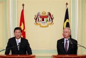 Xi Jinping speaks next to Najib Razak during a joint news conference at Najib's office in Putrajaya