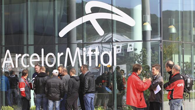 File - In this Oct. 13, 2011 file photo ArcelorMittal steel workers wait outside the company's regional headquarters in Flemalle, near Liege, Belgium. ArcelorMittal steel giant has announced it will close a coke plant and six production lines in a move that is threatening 1,300 jobs. (AP Photo/Yves Logghe, File)