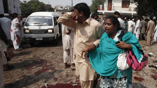 A man and woman mourn the death of their relatives at the site of a blast at a church in Peshawar