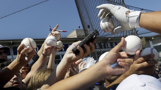 Fans push their baseball towards New York Yankees third baseman Alex Rodriguez to sign before a spring training exhibition baseball game against the Houston Astros in Kissimmee, Fla., Sunday, March 29, 2015. (AP Photo/Carlos Osorio)