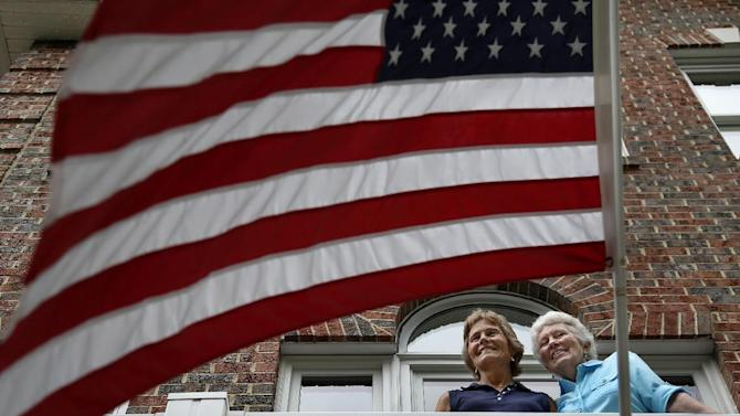 Joan Darrah, left, who served nearly 30 years in the Navy and lived through the Sept. 11 attack of the Pentagon, and her spouse, Lynne Kennedy, pose for a photo at their home in Alexandria, Va., Thursday, June 27, 2013. Just two years ago, gays were prevented from openly serving in the military. Now, with the Supreme Court ruling, same-sex spouses of gay veterans and service members will be able to share in their benefits. (AP Photo/Charles Dharapak)