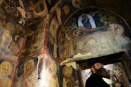 An Orthodox priest looks at icon paintings inside the early 11th century Boyana Church, a UNESCO World Heritage site, in Sofia. It will be among the 10 Bulgarian cities vying for the title of 2019 European Capital of Culture, its mayor said Monday