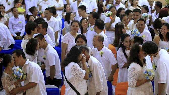 Filipino couples exchange kisses during a mass wedding ceremony ahead of Valentine's Day celebration in Manila