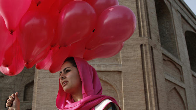 An Afghan woman holds a portion of some 10,000 pink balloons handed out by artists and activists in Kabul, Afghanistan, Saturday, May, 25, 2013. The project brought smiles to surprised Afghans on the street a day after a major Taliban siege on an international compound.(AP Photo/Ahmad Jamshid)