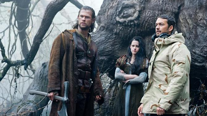 """This film image released by Universal Pictures shows actors Chris Hemsworth, from left, Kristen Stewart and director Rupert Sanders on the set of """"Snow White and the Huntsman"""". Universal Pictures is continuing to pursue a sequel to """"Snow White and the Huntsman"""" in the wake of Kristen Stewart's affair with the film's director. Universal co-chairman Donna Langley said in a statement Wednesday that the studio is """"currently exploring all options to continue the franchise"""" and that reports of Stewart's exit """"are false."""" Since Stewart, who played Snow White in the film, and Rupert Sanders, the married, 41-year-old director of the film last month publically apologized for a tryst caught in photographs, the future of """"Snow White"""" has been uncertain.  (AP Photo/Universal Pictures, Alex Bailey)"""
