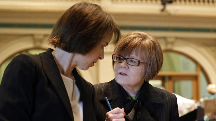 Rep. Claire Levy, D-Boulder, and Rep. Dickie Lee Hullinghorst, D-Longmont, and Majority Leader confer as the Civil Unions Bill is debated  in the House Chamber at the Capitol on Monday, March 11, 2013. The proposal got initial approval with a voice vote in the Democratic-controlled House on Monday. (AP Photo/Ed Andrieski)