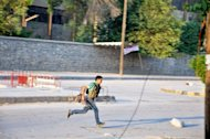 A Syrian rebel runs across a street during clashes with government troops in the Salhin district of the northern city of Aleppo. Syrian troops and rebels poured into commercial capital Aleppo Tuesday as both sides battened down for the long haul after 40 police were killed on day four of a pivotal battle in the nearly 17-month conflict