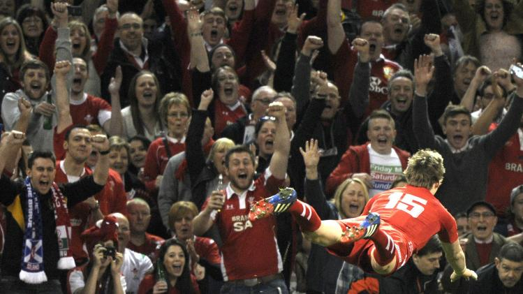 Welsh fans celebrate as Liam Williams scores a try against Scotland, during their Six Nations Championship rugby union match at the Millennium Stadium, Cardiff