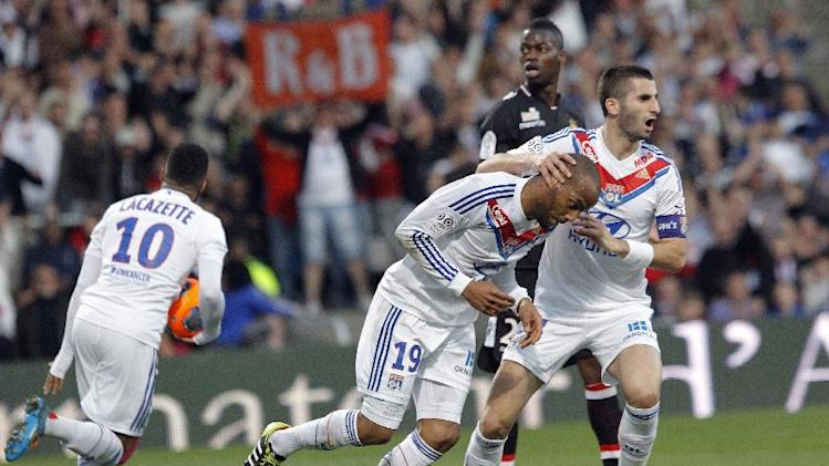 Lyon's Jimmy Briand, center, celebrates with Maxime Gonalons, right, after he scored a goal against Monaco during their French League One soccer match in Lyon, central France, Sunday, March 16, 2014. (AP Photo/Laurent Cipriani)