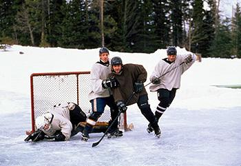 Skank ( Ron Eldard , second from left), the town's sheriff, John Biebe ( Russell Crowe , second from right), and Connor Banks (Michael Buie, right) train for Team Mystery's big game in Mystery, Alaska