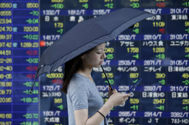 A woman holding a parasol walks past an electronic stock board of a securities firm in Tokyo Friday, Aug. 3, 2012. Japan's Nikkei 225 stock average was down 1.2 percent at 8,553.68 on Friday as Asian stock markets fell after the European Central Bank's policy meeting failed to deliver on bold promises of action to overcome the region's prolonged debt crisis. (AP Photo/Koji Sasahara)