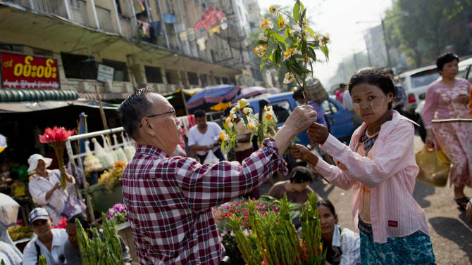 A Chinese origin Myanmar man buys flowers in a street market in Yangon, Myanmar, Tuesday, March 26, 2013. Myanmar's government warned Monday that religious violence could threaten democratic reforms after anti-Muslim mobs rampaged through three more towns in the country's predominantly Buddhist heartland. The mobs destroyed mosques and burned dozens of homes over the weekend despite attempts by the government to stem the nation's latest outbreak of sectarian violence. (AP Photo/Gemunu Amarasinghe)