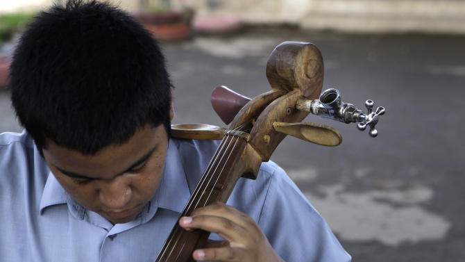 "In this Dec. 11, 2012 photo, a young musician tunes his cello, made from recycled materials, during a practice session with ""The Orchestra of Instruments Recycled From Cateura"" in Cateura, a vast landfill outside Paraguay's capital of Asuncion, Paraguay. Children from the orchestra use instruments fashioned out of recycled materials taken from a landfill where their parents eke out livings as trash-pickers, and about 20 of them regularly perform the music of Beethoven and Mozart, Henry Mancini and the Beatles.  (AP Photo/Jorge Saenz)"