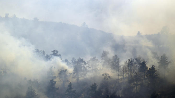 Smoke rises from trees as a wildfire burns out of control at Horsetooth Reservoir east of Fort Collins, Colo., on Friday, March 15, 2013. The 40-acre wildfire burning in gusty winds and warm weather was threatening homes west of Fort Collins on Friday and prompted about 50 people to leave the area. (AP Photo/Ed Andrieski)