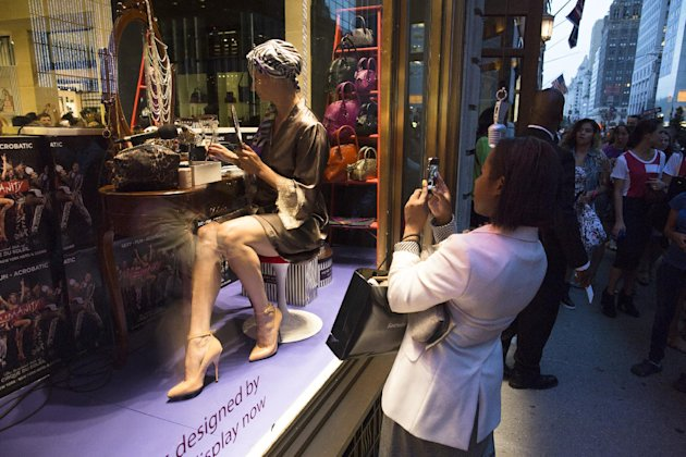 A pedestrian takes a photo of a storefront model during Fashion's Night Out on Fifth Avenue, Thursday, Sept. 6, 2012, in New York. Fashion's Night Out is a global event created to restore consumer confidence and boost the economy of the fashion industry. (AP Photo/John Minchillo)