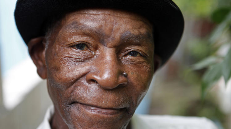 """FILE - In this Aug. 13, 2011 file photo, Joseph """"Powda"""" Bennett, of the band The Jolly Boys, poses for a portrait in Port Antonio, Jamaica. The Jamaican folk musician died in his Caribbean homeland at age 76 on Wednesday, Aug. 20, 2014. The Jolly Boys played a rollicking genre of Jamaican folk music known as Mento. (AP Photo/Caterina Werner, File)"""