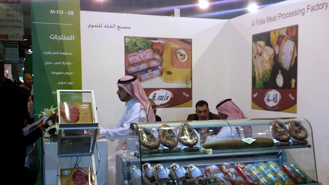 This Monday, Feb. 24, 2014 photo shows a visitor talking with a representative of a halal food producer from Saudi Arabia during a halal food exhibition in Dubai, United Arab Emirates. The global halal food and lifestyle industry is estimated to be worth hundreds of billions of dollars and is multiplying in size as Muslim populations around the world grow. Producers outside the Muslim world _ from Brazil to the U.S. and Australia _ are eager to tap into that market. (AP Photo/Aya Batrawy)