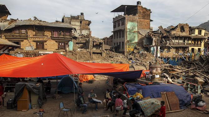 Earthquake survivors gather next to their makeshift shelters, near collapsed houses in Sankhu