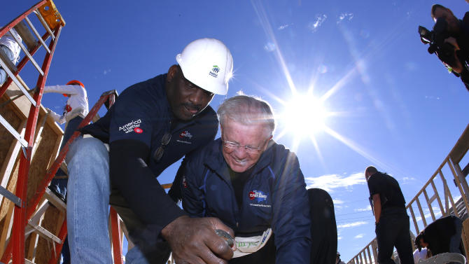 IMAGE DISTRIBUTED FOR MARS CHOCOLATE NORTH AMERICA - Former Washington MVP quarterback, Doug Williams, left, and former Washington coach, Joe Gibbs, celebrate the 25th anniversary of his historic Super Bowl win and helps M&M'S launch their M' Prove America Campaign, which is designed to fund the construction of Habitat for Humanity homes across the country on Friday, Feb. 1, 2013 in New Orleans. Williams led a group of M&M'S associates and customers working on the future home of Ms. Gloria Smith. (Jonathan Bachman / AP Images for Mars Chocolate North America)