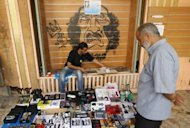 A Libyan vendor sits in front of a graffiti depicting ousted leader Moamer Kadhafi in the eastern city of Benghazi. More than 2.7 million Libyans, or around 80 percent of eligible voters, have registered to participate in the election on July 7