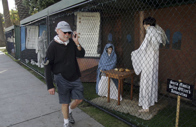 FILE - In this Dec. 13, 2011 file photo, a man walks past two of the traditional Nativity scenes along Ocean Avenue at Palisades Park in Santa Monica, Calif. Avowed atheist Damon Vix last year won two