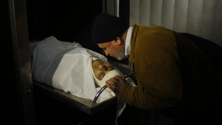 Palestinian man kisses the body of Jihad Hamad at a hospital morgue in Beit Hanoun in the northern Gaza Strip