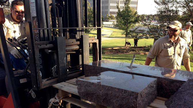 From left, Pete Bennett and Darin Brinson, state workers for the Office of Management and Enterprise Services remove the damaged remains of a Ten Commandments monument from the Oklahoma State Capitol grounds Friday, Oct. 24, 2014 in Oklahoma City. Authorities say someone drove across the Oklahoma Capitol lawn and knocked over the monument. The American Civil Liberties Union had been suing to have the monument removed, arguing it violates the Oklahoma Constitution. (AP Photo/Sean Murphy)