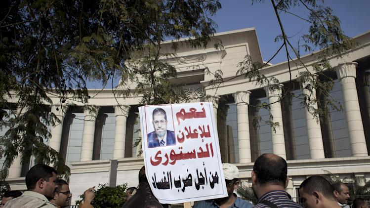 "A supporter of Egyptian President Mohammed Morsi holds a banner with his picture and Arabic that reads, ""yes for the constitutional declaration to stop corruption,"" during a protest in front of Egypt's top court, in Cairo, Egypt, Monday, Dec. 3, 2012. The Egyptian president's top legal adviser says the country's election commission has begun preparations for the referendum on Dec. 15 on a highly contentious draft constitution. (AP Photo/Nasser Nasser)"