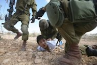 File photo shows a boy is arrested by Israeli soldiers for throwing stones during a protest near the West Bank city of Hebron. Stone throwing, a symbol of Palestinian resistance to the Israeli occupation, began among the youth of Jabaliya refugee camp in the northern Gaza Strip during the first Palestinian uprising (1987-1993)
