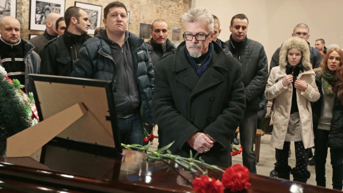Eduard Limonov, center, one of the leaders of opposition the Other Russia movement pays his last respects to Alexander Dolmatov during a mourning ceremony in Moscow, Russia, Wednesday, Feb. 6, 2013. Relatives held funeral services Monday for Dolmatov, 36, who Dutch authorities say killed himself in a Rotterdam asylum deportation center last month. The Russian opposition activist who committed suicide has been laid to rest amid ongoing controversy over his treatment from the Dutch asylum system. (AP Photo/Mikhail Metzel)