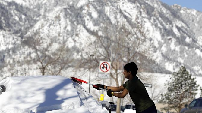 Adnan Reza, a senior engineering student at the University of Colorado, from Dhaka, Bangladesh, removes the snow from his car on a sunny morning following a winter storm, in Boulder, Colo., Monday Feb. 25, 2013. Coloradoans are digging out from a major snowstorm that canceled flights, delayed opening of Denver city offices and piled up snow as much as two-feet deep.(AP Photo/Brennan Linsley)