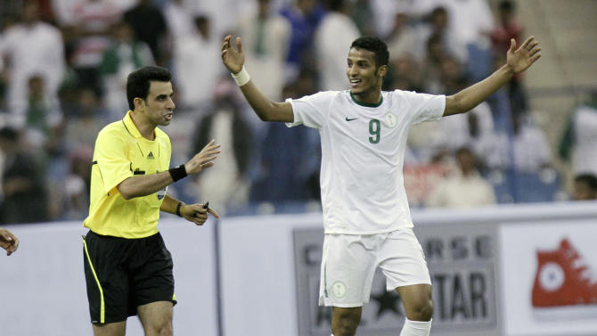 Saudi Arabia's Naif Hazazi, right, reacts with the Referee Torky Mohsen from Iran during the 2014 FIFA World Cup Asia qualifying soccer match against Saudi Arabia at King Fahd stadium in Riyadh, Saudi Arabia, Tuesday, Nov. 15, 2011. (AP Photo/Hassan Ammar)