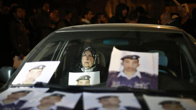 Mother of Islamic State captive Jordanian pilot Muath al-Kasaesbeh holds his picture as she takes part in a demonstration in Amman