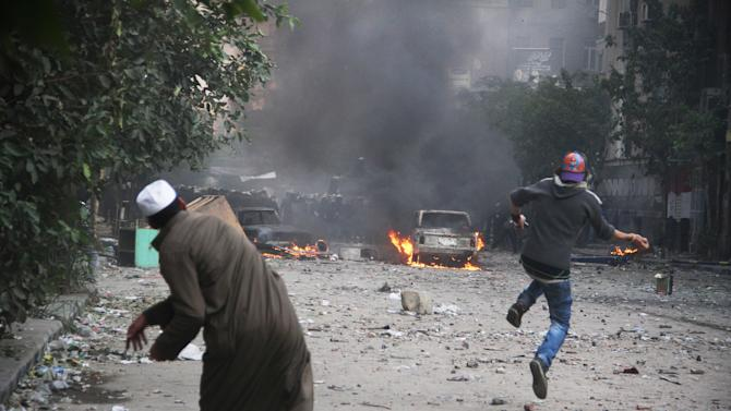 Two Egyptian protesters throw rocks toward Egyptian riot police in Cairo, Egypt, Monday, Nov. 21, 2011. Security forces fired tear gas and clashed Monday with several thousand protesters in Cairo's Tahrir Square in the third straight day of violence that has killed dozens of people and has turned into the most sustained challenge yet to the rule of Egypt's military. (AP Photo)