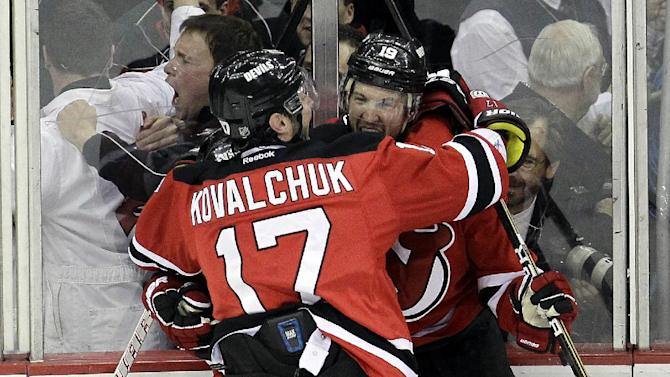 New Jersey Devils' Travis Zajac, right, celebrates with teammate Ilya Kovalchuk, of Russia, and another player after Zajac's game-winning goal in overtime against the Florida Panthers in Game 6 of a first-round NHL hockey Stanley Cup playoff series, Tuesday, April 24, 2012, in Newark, N.J. The Devils won 3-2, sending the series to a seventh game. (AP Photo/Julio Cortez)