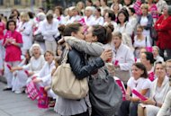 Two women kiss in front of people taking part in a demonstration against gay marriage and adoption by same-sex couples on October 23, 2012 in Marseille, southeastern France. Passions and tensions are rising in France ahead of an expected giant weekend rally against the government's plan to legalise same-sex marriage and adoption that has angered influential Catholic and Muslim groups