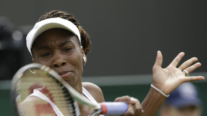 Venus Williams of the United States returns a shot to Elena Vesnina of Russia during a first round women's singles match at the All England Lawn Tennis Championships at Wimbledon, England, Monday, June 25, 2012. (AP Photo/Alastair Grant)