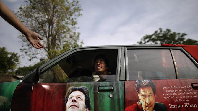 A Pakistani supporter of former cricket star-turned-politician, and leader of Pakistan Tehreek-e-Insaf party, Imran Khan, talks with another from his car decorated with pictures bearing the image of Khan, in Islamabad, Pakistan, Friday, May 10, 2013. An especially violent spate of killings, kidnappings and bombings marred the run-up to Pakistan's nationwide election, capped Thursday by the abduction of the son of a former prime minister as he was rallying supporters on the last day of campaigning before the historic vote. (AP Photo/Muhammed Muheisen)