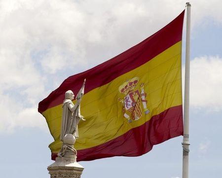 A statue of Christopher Columbus with an extended hand is seen in front of a Spanish flag in central Madrid