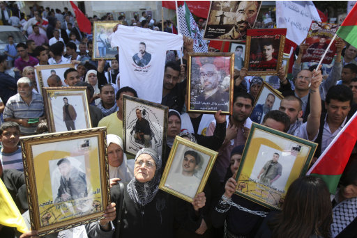 Palestinians hold photographs of prisoners jailed in Israel, during a rally marking the annual prisoners' day in the West Bank city of Nablus, Tuesday, April 17, 2012. The Israeli prison service said Tuesday hundreds of Palestinian prisoners have launched a hunger strike to mark the Palestinians' annual prisoners day. (AP Photo/Nasser Ishtayeh)