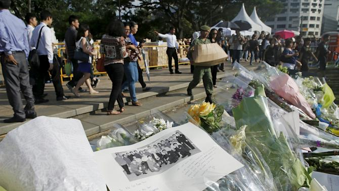 People pass a row of flowers and tributes, as they queue up to pay their respects to the late first prime minister Lee Kuan Yew, at the Parliament House in Singapore