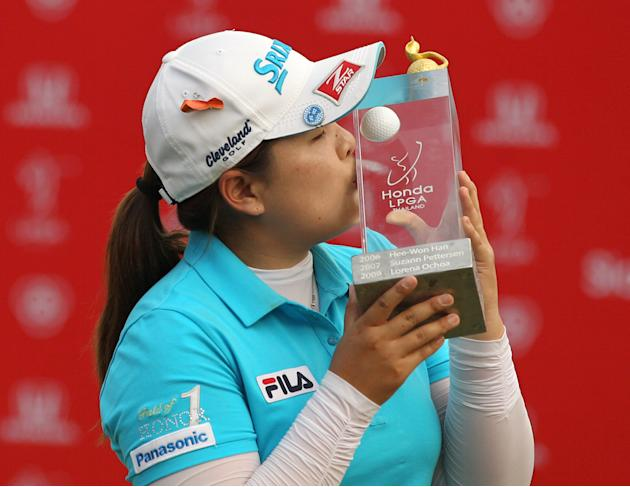 Inbee Park of South Korea kisses her winner's trophy during the awarding ceremony of the LPGA Thailand golf tournament in Pattaya, southern Thailand, Sunday, Feb. 24, 2013. (AP Photo/Sakchai Lalit)