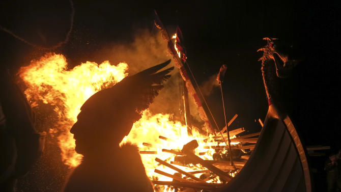 In this photo taken March 14, 2014, a man dressed as a Viking is silhouetted against a burning mock Viking ship as they take part in the annual Up Helly Aa, Viking fire festival in Gulberwick, Shetland Islands north of mainland Scotland. The fearsome-looking participants in the festival live in Scotland's remote Shetland Islands, a wind-whipped northern archipelago where many claim descent from Scandinavian raiders. They are cool to the idea of Scotland leaving Britain to form an independent nation, and determined that their rugged islands will retain their autonomy whatever the outcome of September's referendum. (AP Photo/Jill Lawless)