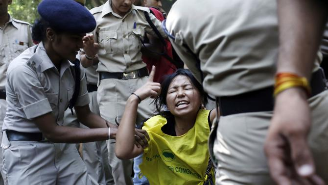 A Tibetan exile is detained by police during a protest outside the venue of a meeting between Chinese President Xi and Indian PM Modi in New Delhi