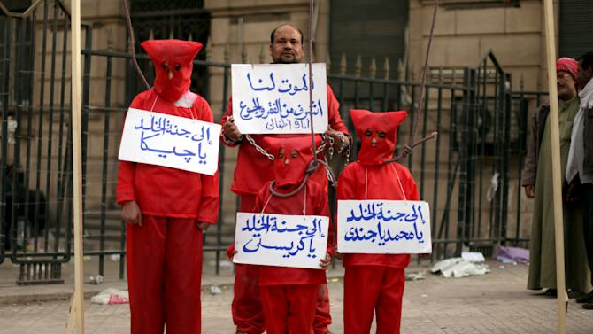 """An Egyptian man with his three children wear red during a symbolic hanging at an anti-government protest in front of Egypt's high court building in downtown Cairo, Friday, Feb. 22, 2013. The Arabic writing on the banners reads, """"death is more honorable for me and my children than poverty and hunger,"""" and """" Jeeka, Christy and Mohammed to heaven.""""  Egypt's president called multi-stage parliamentary elections beginning in April but a key opposition leader warned Friday that the vote may only inflame tensions unless there are serious political talks first.(AP Photo/Khalil Hamra)"""