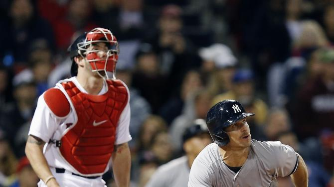 New York Yankees' Brett Gardner, right, watches his three-run home run in front of Boston Red Sox's Blake Swihart during the sixth inning of a baseball game in Boston, Sunday, May 3, 2015. (AP Photo/Michael Dwyer)