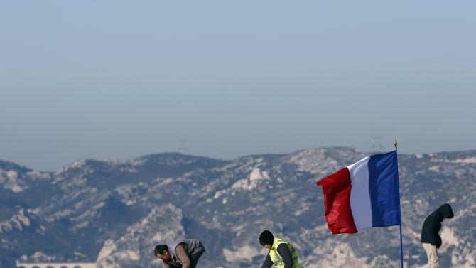 A French national flag flies as workers stand on the roof of the Villa Mediterranee in Marseille