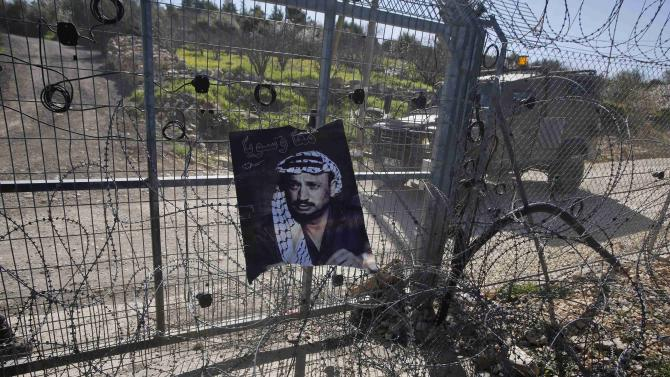 A poster depicting late Palestinian leader Yasser Arafat hangs on a settlement gate during a protest by Palestinians against Jewish settlements, in Biet Ommar