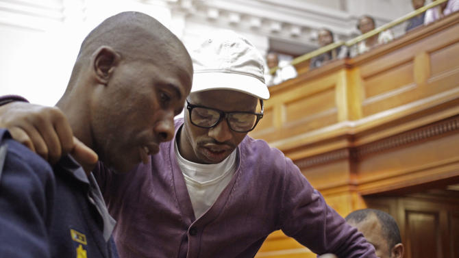 """Xolile Mngeni, center, arrives in court before being sentenced at Cape Town, South Africa, Wednesday, Dec. 5,  2012. A South African judge sentenced the triggerman in the 2010 honeymoon slaying of a Swedish bride to life in prison Wednesday, calling the shooter """"a merciless and evil person"""" who deserved the maximum punishment for his crime. Prosecutors say the newlywed's British husband orchestrated the November 2010 killing. Judge Robert Henney did not hold back his contempt while sentencing Xolile Mngeni for the killing of 28-year-old Anni Dewani. Henney said that the shooter showed no remorse. (AP Photo/Schalk van Zuydam)"""
